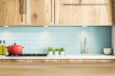 Blue tile kitchen interior with wooden countertops and cabinets, a red cooking pot and several potted plants. 3d rendering mock up