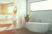 Luxusní koupelna roh s bílými zdmi, černá dlažba, bílá vana a umyvadlo. Úzký vodorovný okno. Skandinávský styl. Žena v pyžamu 3d vykreslování laděných dvojitá expozice obrazu