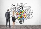 Geschäftsfrau und Geschäftsmann blicken auf eine helle, bunte Glühbirne mit einem Gehirn darin. Businessplan und Ideensymbole auf einer Betonwand drumherum gezeichnet.