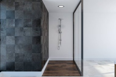 Glass shower stall in a spacious bathroom interior with black tile and white walls, a white and wooden floor and mock up wall fragment 3d rendering