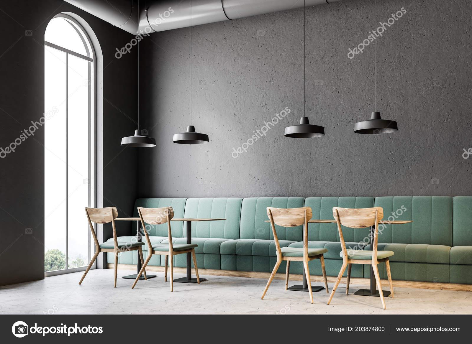 Interni café parete grigio scuro con pavimento cemento tavoli legno