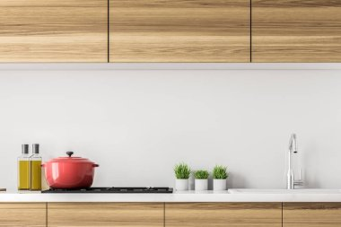 Wooden kitchen countertops with a built in cooker, a pot on it and small plants. Olive oil. Concept of cooking at home and family values. 3d rendering mock up