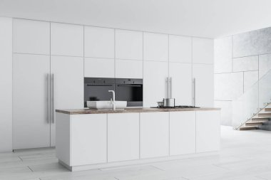 Modern kitchen corner with white countertops and cupboards, and a concrete floor. A staircase 3d rendering mock up