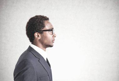 Side view of a young handsome African American businessman wearing glasses and a gray suit. A concrete wall background. Mock up