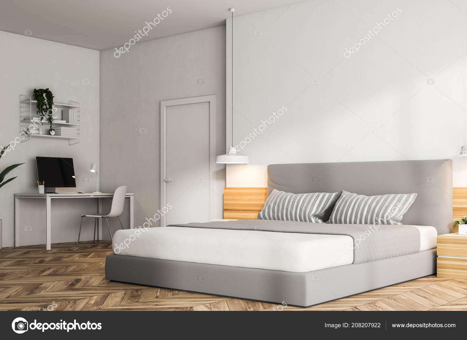 Hoek van een moderne slaapkamer met witte muren een houten