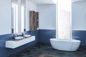 Fotografia Modern bathroom corner with white and blue walls, a tiled floor, a white bathtub standing under the window, a double sink and shelves. 3d rendering mock up