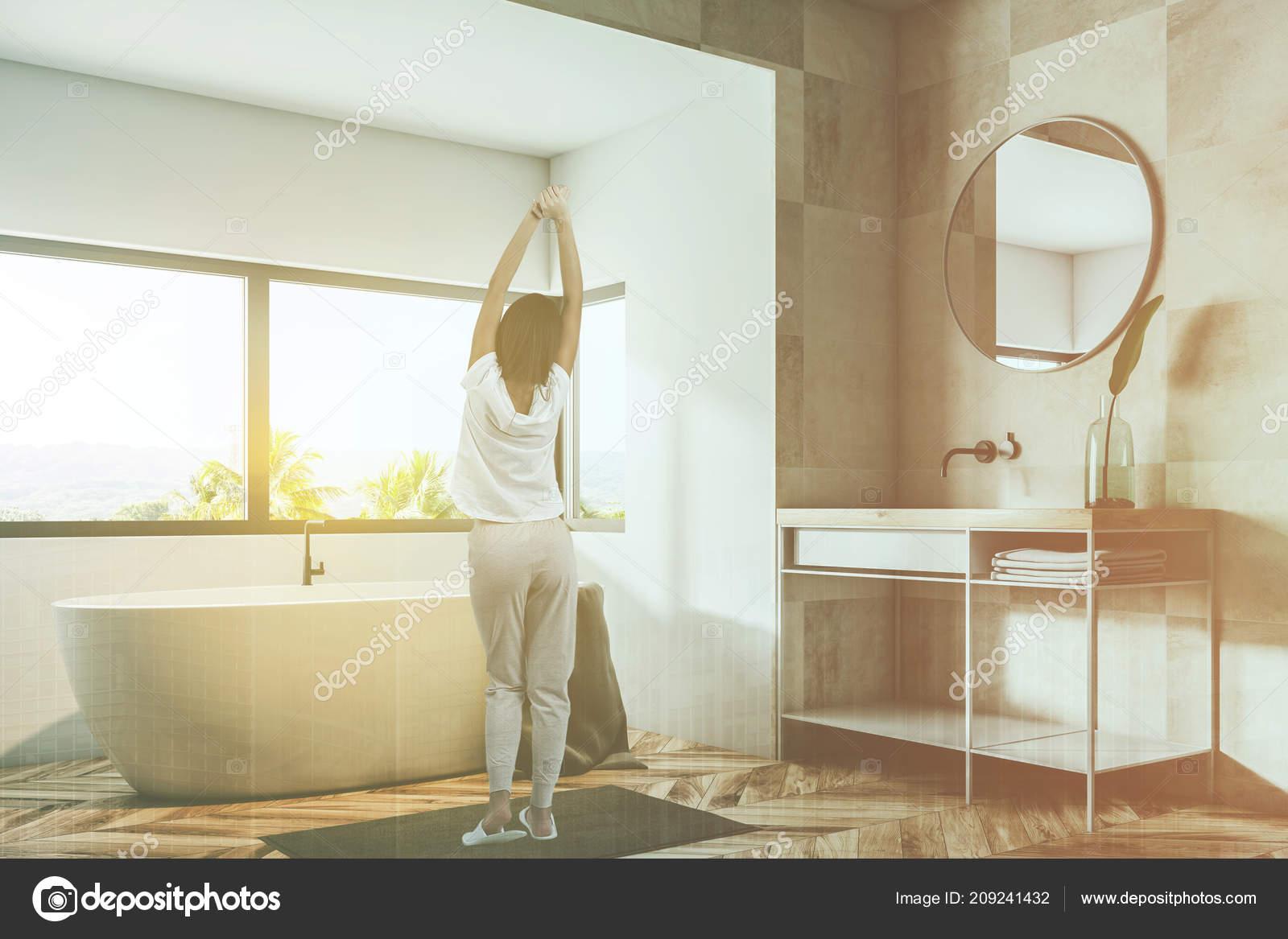 Donna angolo del bagno con beige piastrelle pareti pavimento legno