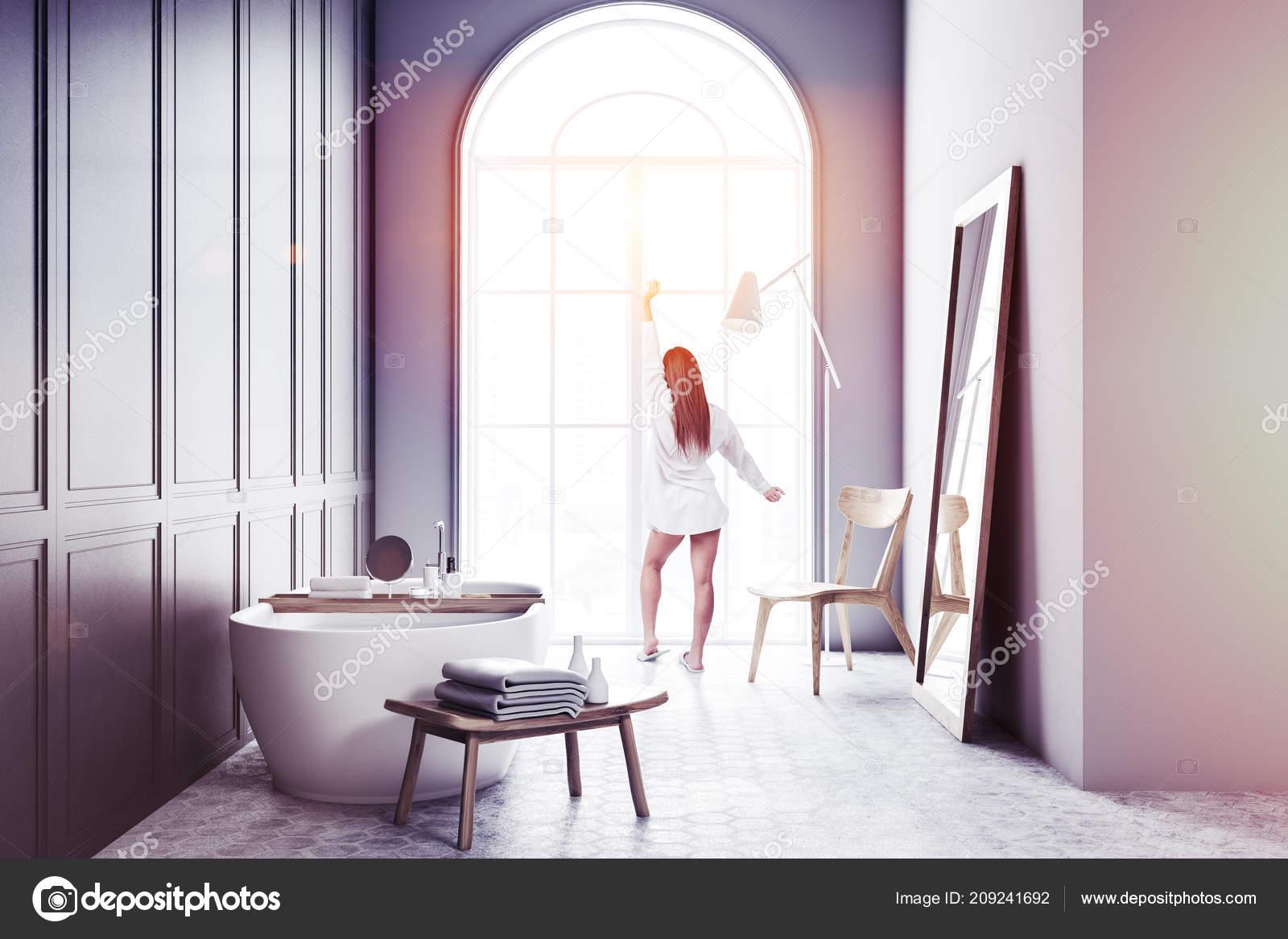 Donna vicino all elegante vasca bagno bianca riempita acqua piedi
