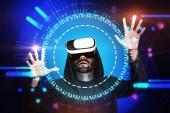 Vousatý mladík na sobě černou mikinu a vr brýle interakce s rozhraním zářící modré hud. Koncept hi tech a inovace. Tónovaný obrázek dvojexpozicí mock-up