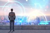 Pohled zezadu na podnikatel stojí na balkoně při pohledu na futuristické zářící ikony. Abstraktní Hud a infograph městské obloze. Tónovaný obrázek dvojexpozicí mock-up prvky tohoto obrázku jsou podle Nasa