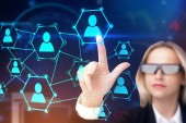 Blonde businesswoman in AI glasses touching hr network hologram interface. Blurred office background. Toned image double exposure mock up