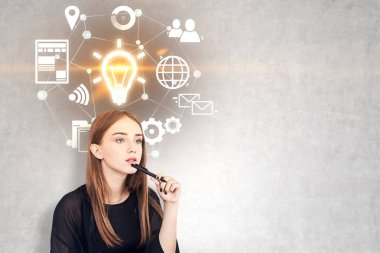 Pensive young woman with long fair hair holding a pen near her chin. A concrete wall background with glowing light bulb and business icons. Mock up