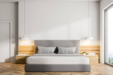 Interior of a modern bedroom with white walls, a wooden floor, a double bed and two bedside tables with lamps. Loft window. 3d rendering mock up