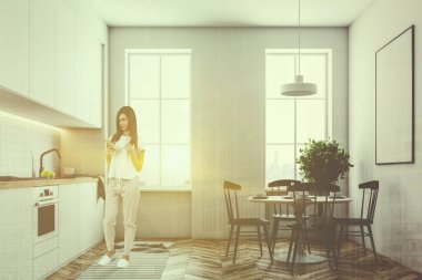 Woman in kitchen interior with white walls, large windows, a wooden floor and white countertops. A round table with chairs and a poster on the wall. 3d rendering mock up toned image double exposure