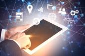 Fotografie Händen der Geschäftsmann berühren Tablet-Bildschirm über dunkelblauen Hintergrund. Immersive Schnittstelle mit einem Netzwerk Hologramm und Business Symbole Vordergrund. Getönten Bild Doppelbelichtung