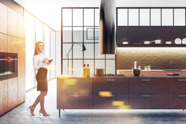 Blond businesswoman with coffee in Modern gray wall kitchen interior with panoramic windows, hexagonal gray tile floor and brown countertops with built in appliances. 3d rendering mock up toned image
