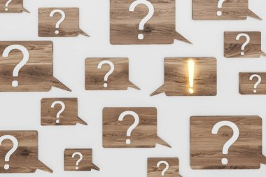 White question and exclamation marks on wooden speech bubbles over gray background. Shining exclamation mark. FAQ concept and looking for an answer. 3d rendering