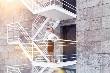 Side view of modern building exterior with concrete brick walls, grey doors and emergency exit stairs with blonde businesswoman using binoculars. 3d rendering mock up toned image double exposure