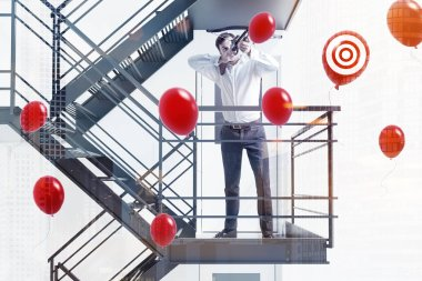 Businessman with crossbow shooting red balloons with target standing on emergency stairs of a white building. Successful startup project concept. 3d rendering mock up toned image double exposure