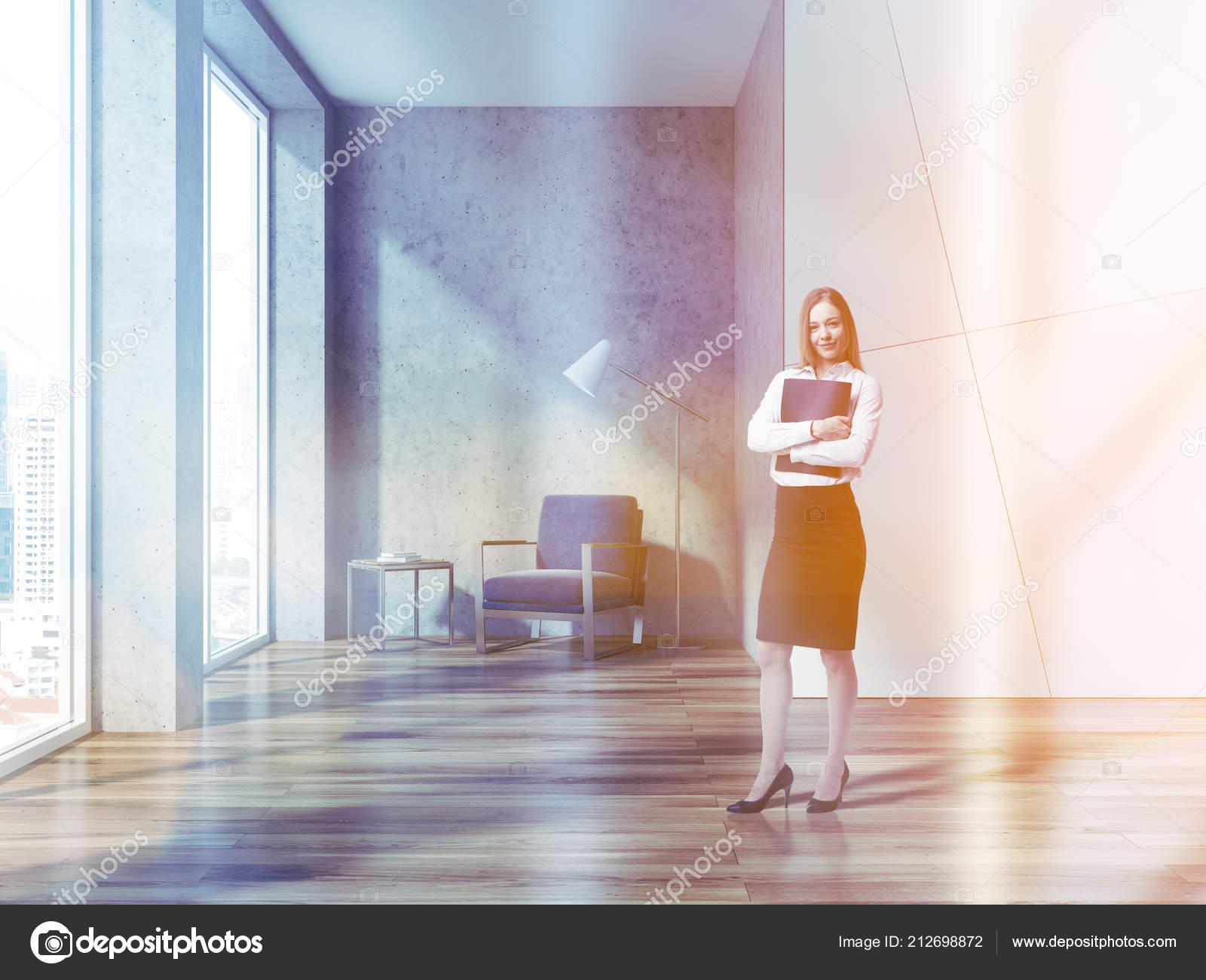 Gai femme affaires permanent dans hall bureau blanc béton mur