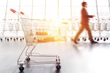 Supermarket trolley with mock up products over long supermarket carts row standing along a panoramic window. Businessman walking. Concept of marketing. 3d rendering copy space toned image