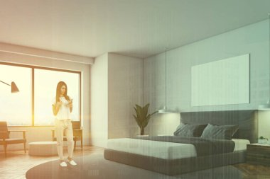 Woman looking at phone in minimalistic bedroom with round carpet, masterbed, night stand and round coffee table with gray armchairs. Toned image double exposure horizontal mock up poster