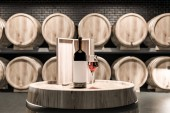 Photo Close up of wine keg with wine bottle, wooden box and glass of red wine standing in a black brick cellar with rows of kegs in the background. 3d rendering