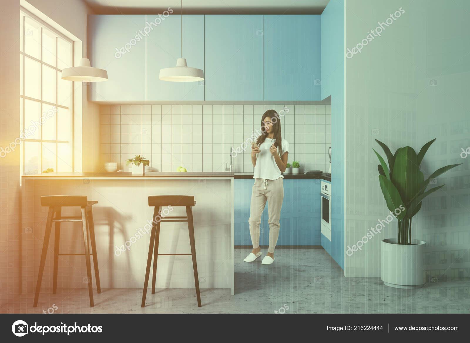Donna dai capelli scura smartphone piedi cucina piastrelle bianche