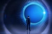 Zadní pohled mladého muže v obleku při pohledu na působivé rozhraní kolem s modrými a bílými hud. Hi tech a vr koncepce. Laděných prostor kopie dvojitá expozice obrazu