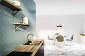 Fényképek Szürke és fehér konyha belső, fehér márvány padló, a fekete és fából készült munkalapok, a fehér kerek asztal székekkel és virágágyások közelében a falra. Polcok a falra. 3D-leképezés