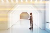 Podnikatel s doklady ve futuristické prázdné bílé hexagonální tvar chodby s osvětlený strop a stěny. Koncept kreativity v architektuře a hi tech. Toned obrázek