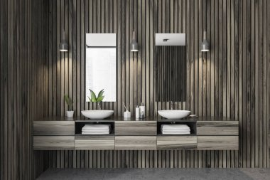 Double sink in modern bathroom interior with dark wooden walls and gray floor. Vertical narrow mirrors and stylish ceiling lamps. 3d rendering
