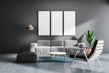 Gray living room interior with concrete floor, gray armchair and sofa, a round coffee table with row of vertical mock up poster frames. 3d rendering
