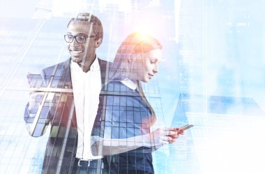 Charismatic african american businessman and his beautiful and smart colleague standing with cell phones over blurred city background. Business communication concept. Toned image double exposure