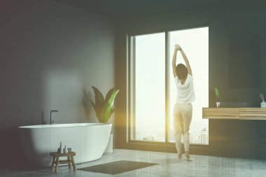 Woman standing in loft bathroom corner with gray walls, concrete floor, white bathtub and sink with vertical mirror. Toned image double exposure