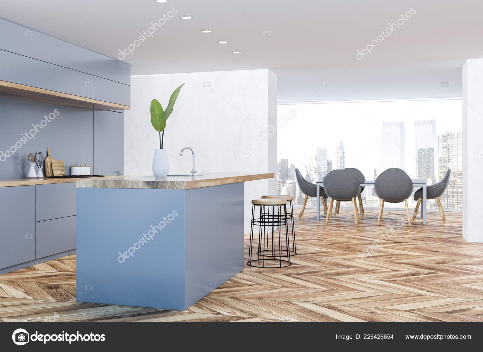 cb675383840d Esquina de la cocina y comedor con paredes blancas, piso de madera,  encimeras de gris, barra con taburetes redondeos y mesa de comedor con  sillas en el ...