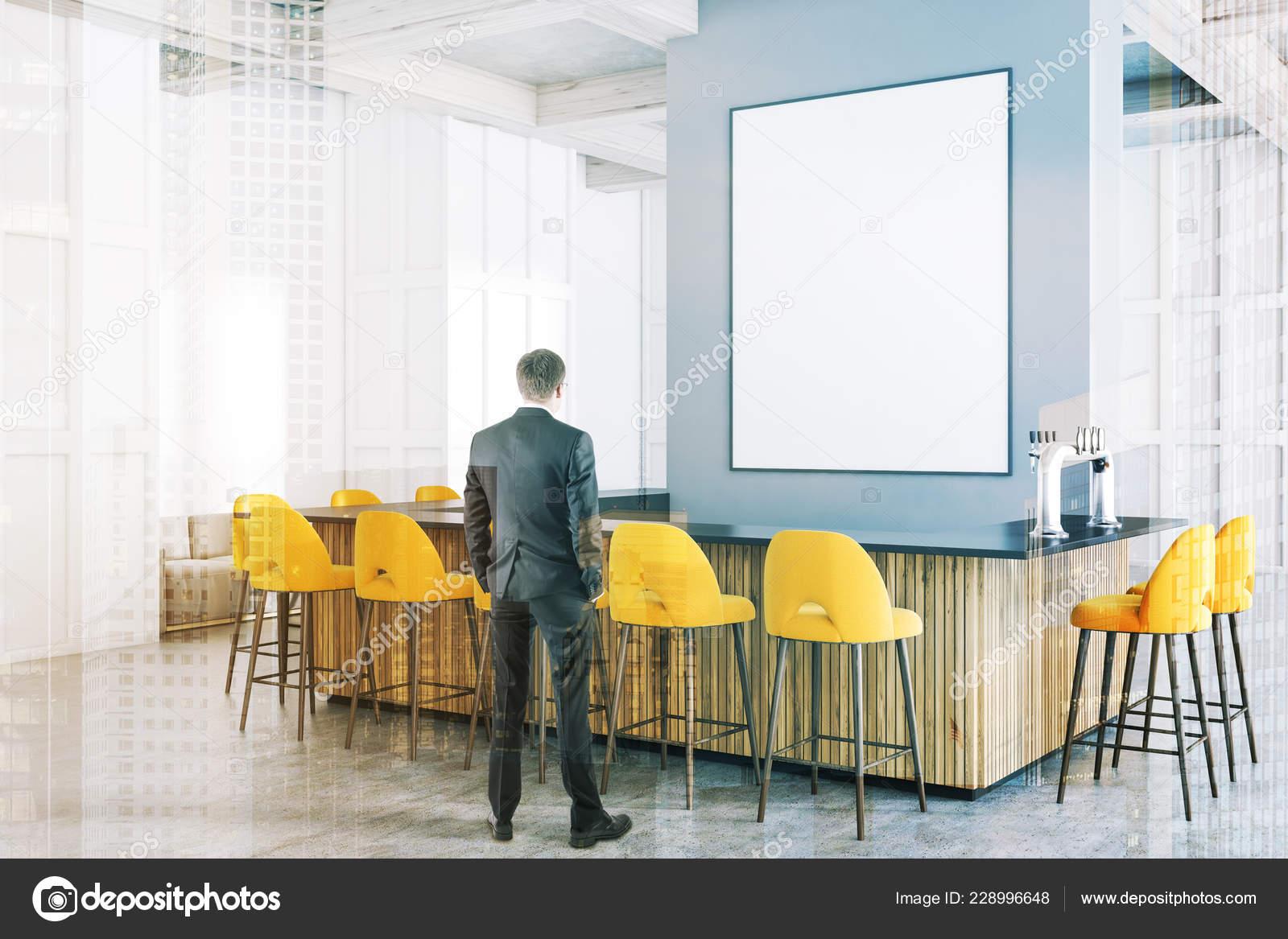 80b316d2550a Hombre en la esquina de bar moderno con paredes blancas, piso de concreto,  grandes ventanas, madera y gris de la barra con taburetes amarillo de pie  cerca ...