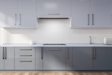 Minimalistic kitchen interior with white walls, wooden floor, dark gray countertops with built in cooker and sink and light gray cupboards. 3d rendering