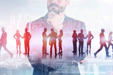 Transparent portrait of unrecognizable pensive businessman with silhouettes of his team members over cityscape background. Concept of leadership. Toned image double exposure