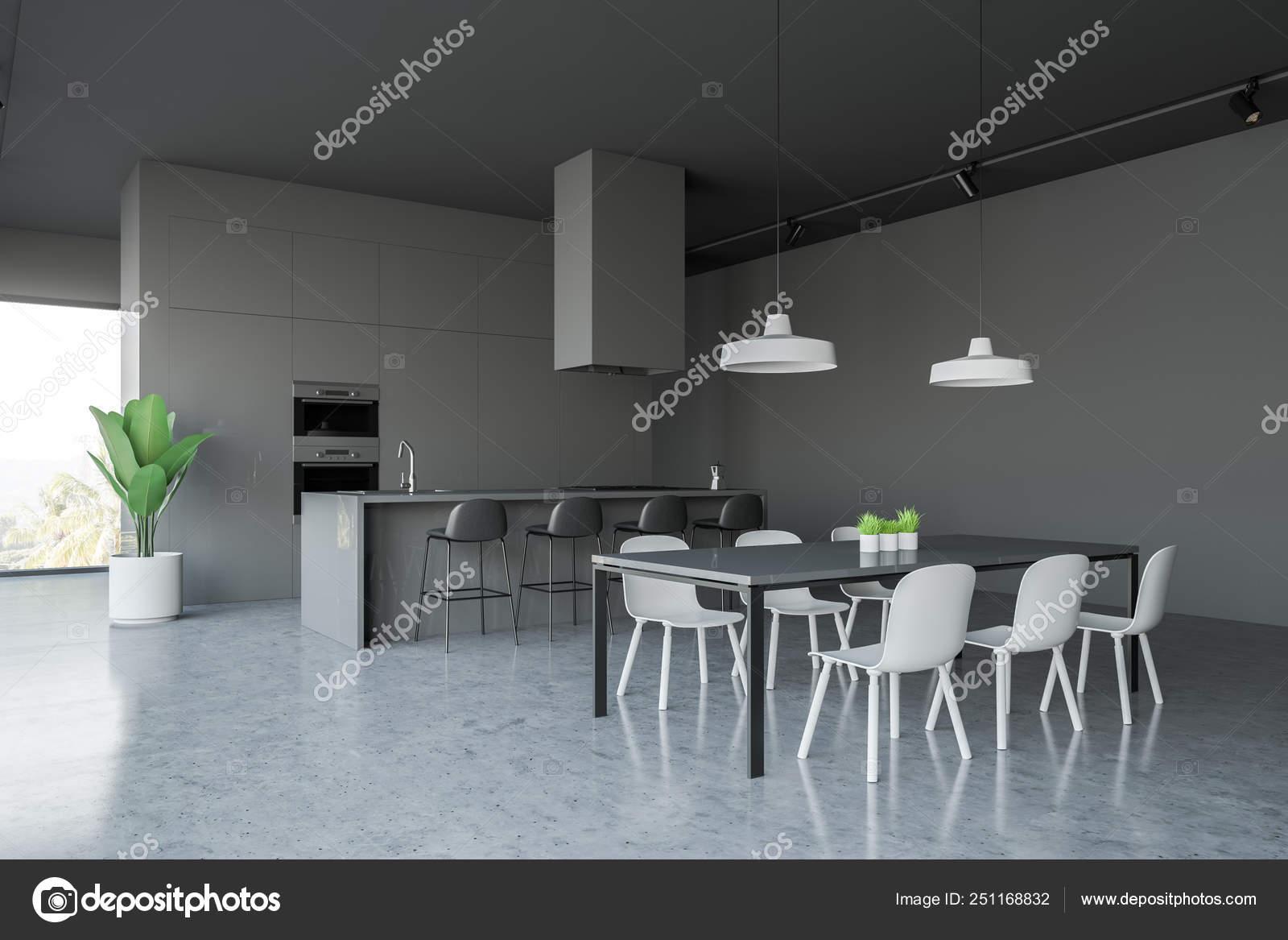 ab25ee0d184c Esquina de la cocina moderna con paredes gris, suelo de hormigón gris barra  con taburetes y mesa negra con sillas. Construido en hornos.