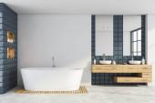 Interiér moderní koupelny s bílými a šedými dlaždicovými stěnami, betonovou podlahou, pohodlným dvojitým umyvadlem stojícím na dřevěné desce se dvěma zrcadly a vanou. 3D vykreslování