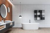 Oldalnézet a modern fürdőszoba fehér és barna csempe falak, csempézett padló, kényelmes dupla mosogató álló szürke pult kerek tükrök és fehér fürdőkád. 3D-s renderelés