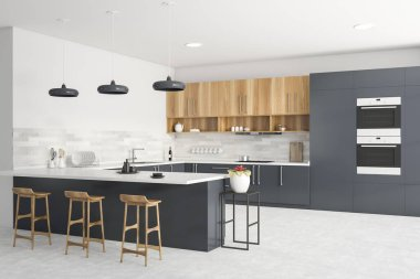 Corner of modern kitchen with grey and white walls, grey countertops, wooden cupboards, bar with stools, two ovens and window with blurry cityscape. 3d rendering stock vector