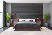 Interiér moderní hlavní ložnice s šedými a dřevěnými stěnami, betonovou podlahou, pohodlnou postelí velikosti king size s červenými nočními stolky a oknem s rozmazaným panoramatem. 3D vykreslování