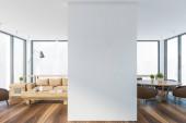 Belső tér a modern nappali fehér falakkal, kényelmes bézs kanapé mellett áll dohányzóasztal és étkező kerek asztal és barna fotelek mellette. Homályos városkép. 3D-s renderelés