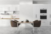 Interiér moderní kuchyně s bílými a cihlovými zdmi, betonovou podlahou, bílými skříněmi a pulty, vestavěný v pecích a jídelním stole s hnědými křesly. 3D vykreslování