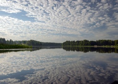 beautiful summer morning landscape on the lake, beautiful clouds and wonderful reflections in the lake mirror, summer morning by the water