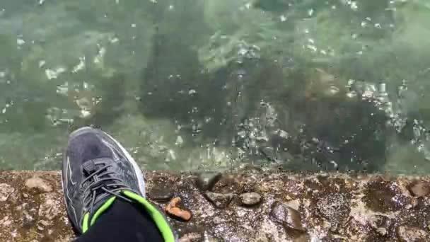 Sneaker am Meer, der sich vom Laufen befreit. Ego-Ansicht der Strandpromenade Turnschuh. Bunt.