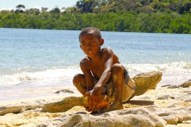 Poor malagasy boy breaking coconuts on the beach