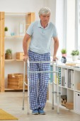 Photo Portrait of senior man in domestic clothing trying to walk with walker in the room at home